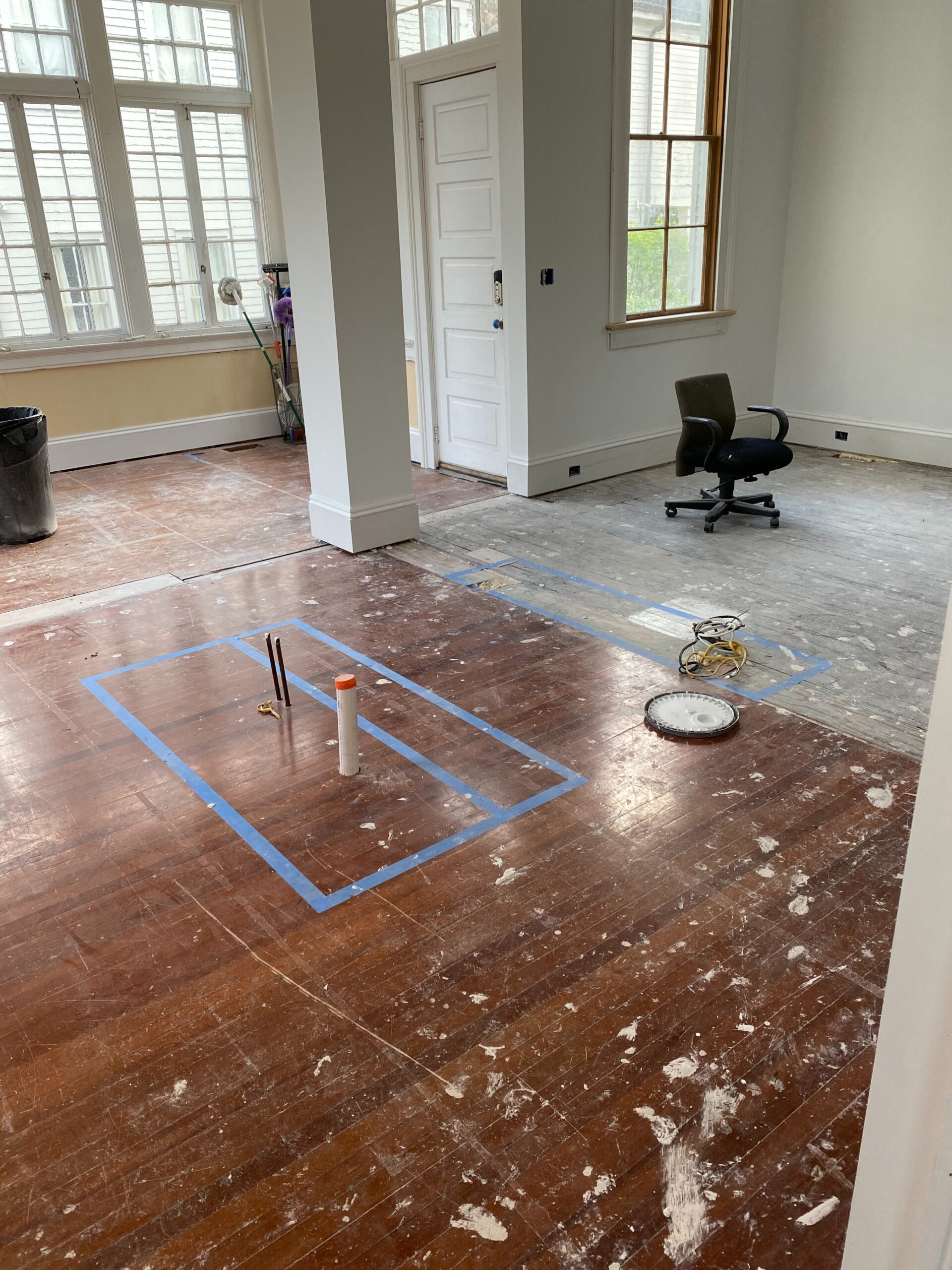 Before photo in living area with a column and red heart of pine hardwood floors