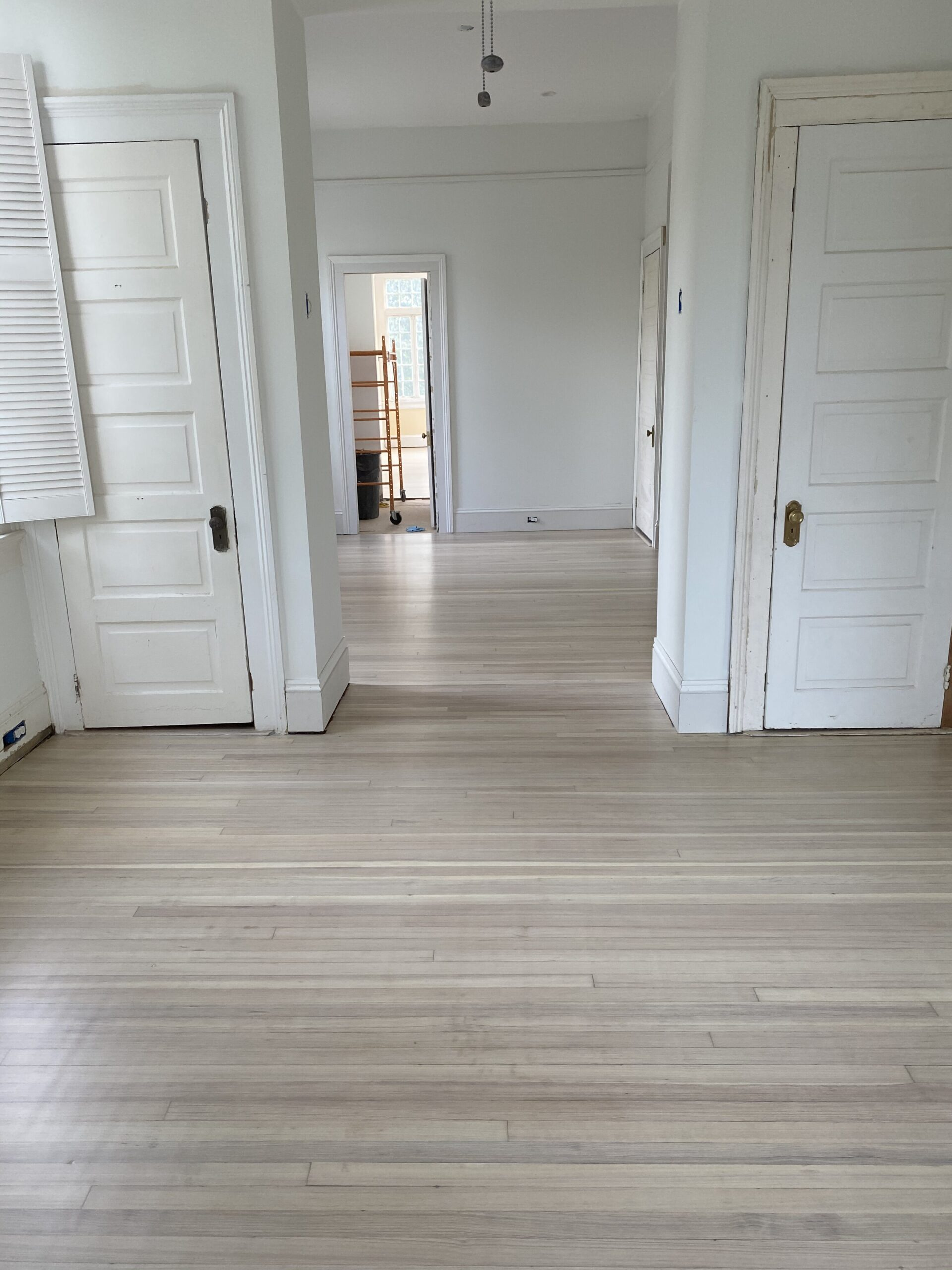 Two rooms of bleached with a white wash hardwood flooring