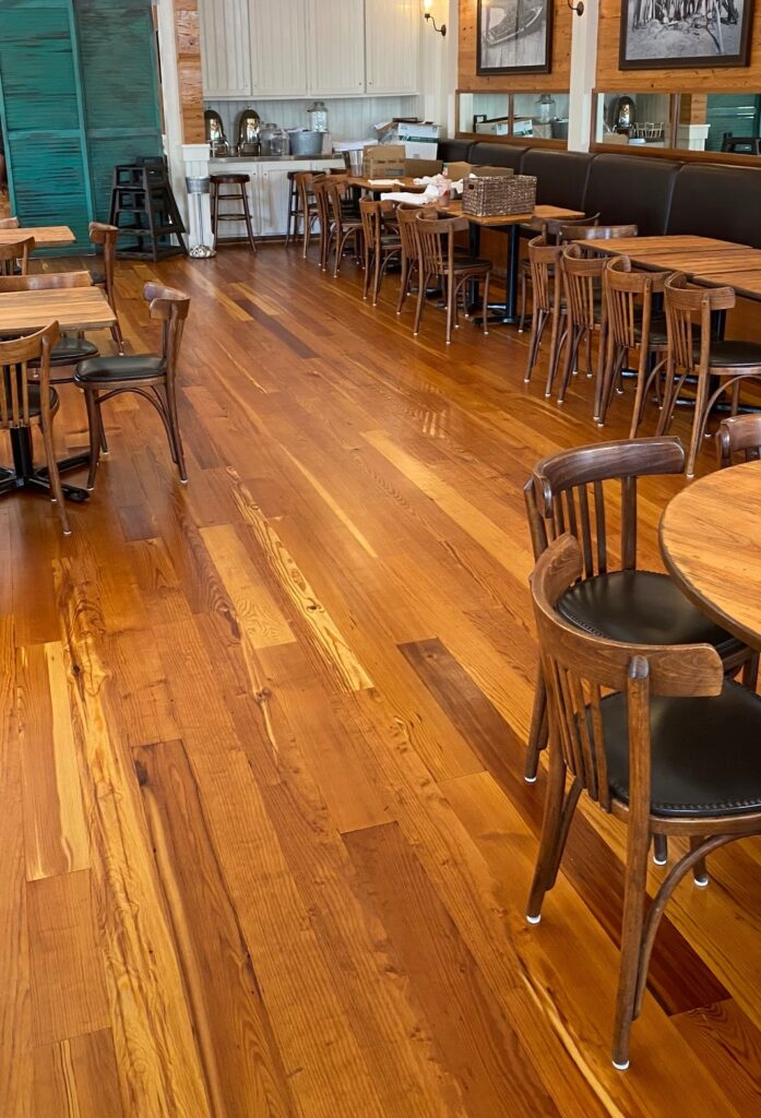 Photo of refinished antique heart of pine floors in a restaurant. Tables and chairs set up for dining.