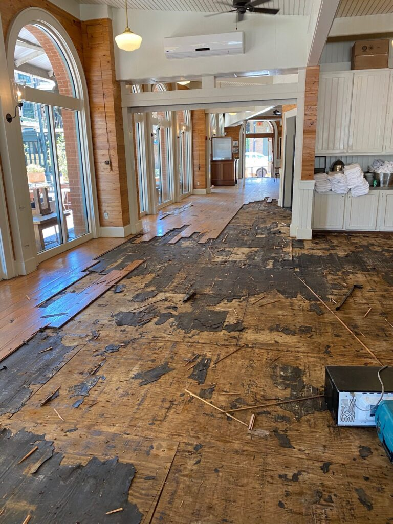 Existing hardwood flooring in a restaurant in the process of removal to be replaced with new hardwood flooring.