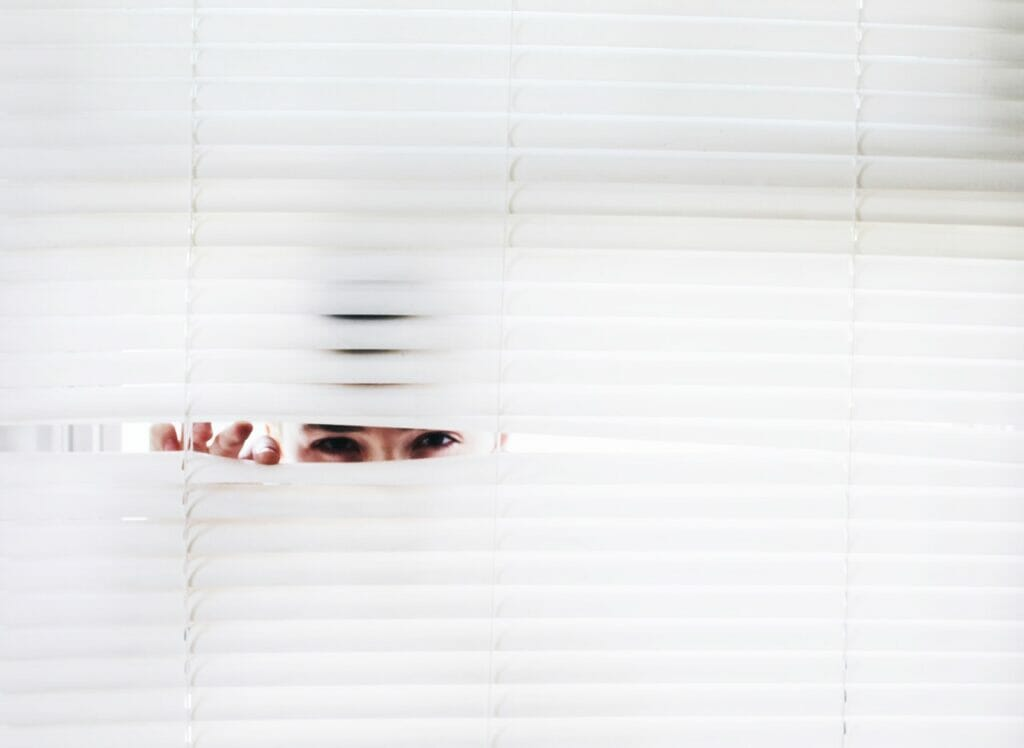 insurance adjuster peeking through window blinds
