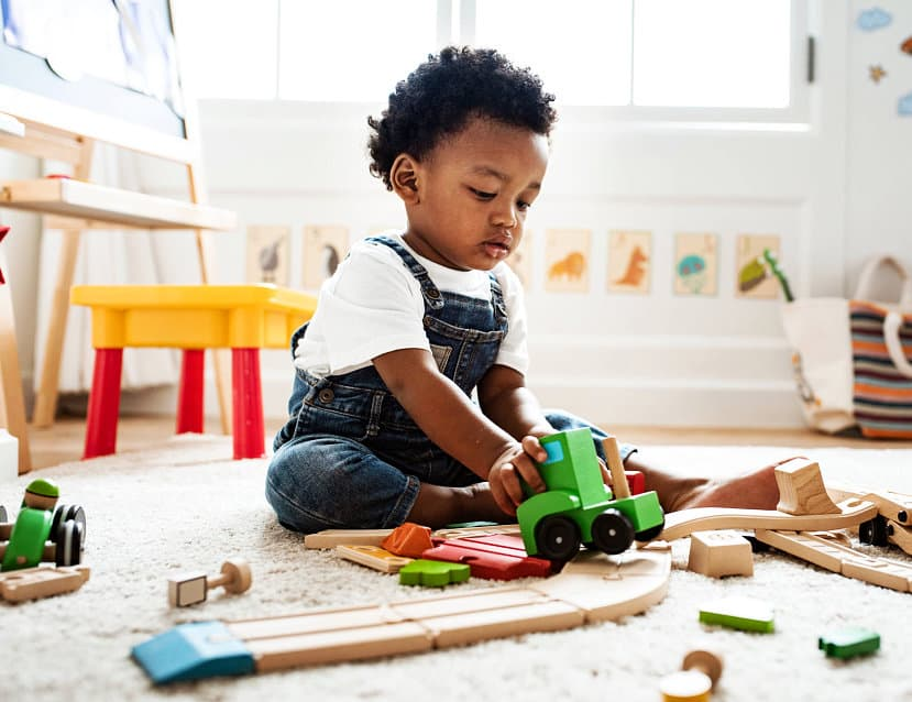 toddler playing with car toys
