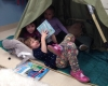 group of kids reading inside the tent