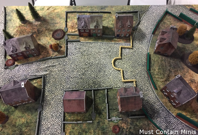 A beautiful Battlefield for Bolt Action using Plastcraft Games Buildings and a Cigar Box Battle Mat