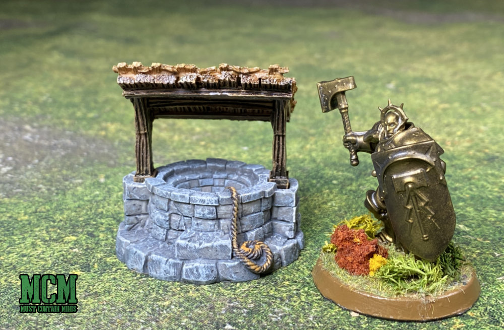 Monster Fight Club's Village Well along side an Age of Sigmar Miniature