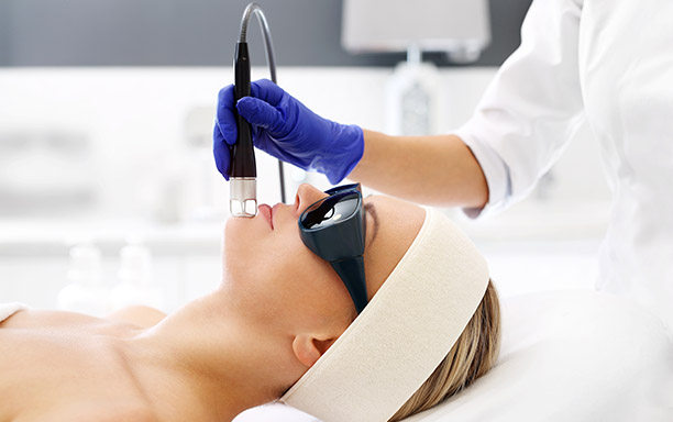 A woman in a beauty salon during a laser treatment.