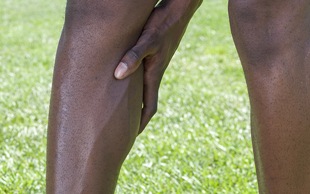 Closeup of shin and calf muscle of lean African American man as he holds calf muscle to alleviate pain