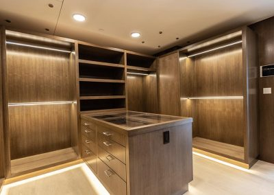 light strips and wood finished master walk-in closet