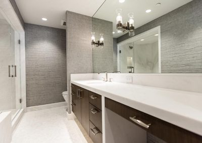 bathroom with large vanity mirror and countertop and cabinets