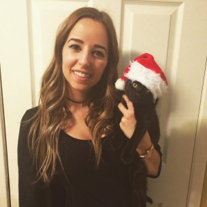 female animal care attendant holding a cat with a santa hat