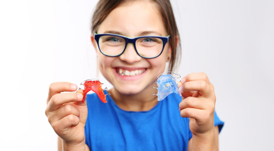 adolescent girl with retainer in hand