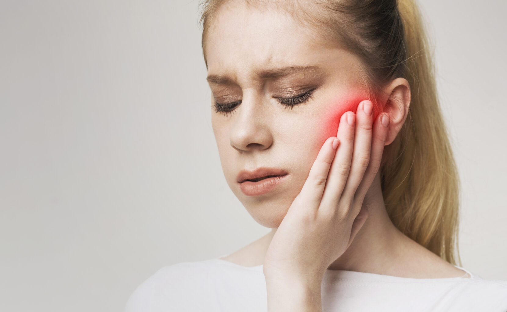 young woman touching face because of jaw pain on white background