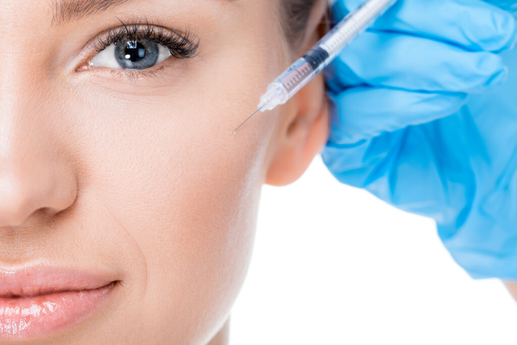 woman receiving BOTOX injection by doctor with blue glove