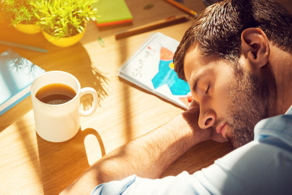 man sleeping on desk with cup of coffee