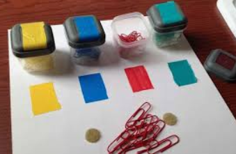 Colored paperclips and small square painted boxes to help students