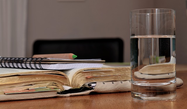 Placeholder image of open book, notepad and glass of water.