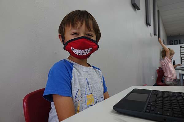 Kindergarten boy smiling with a mask