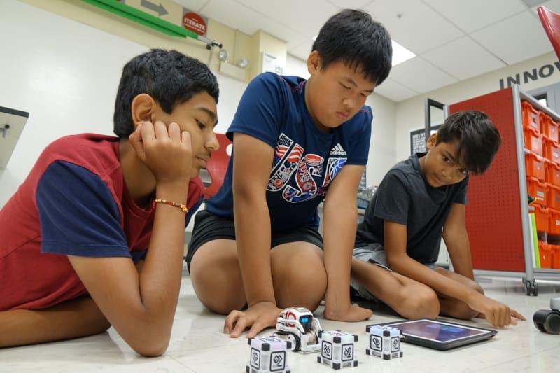 3 middle school boys coding a robot