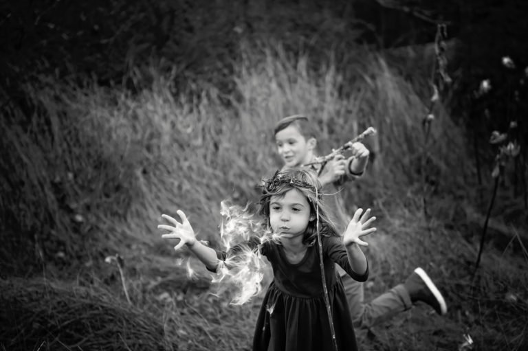 photo of children running and blowing dandelions