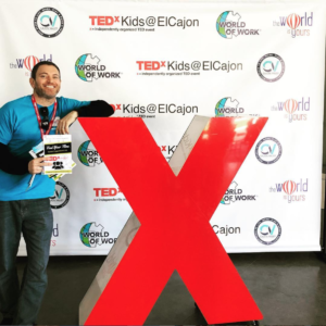 Winston Widdes, author with book standing in front of TedX sign - TEDx