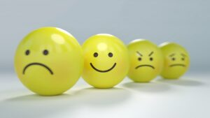 Be a boss of your life attitude, smiley face ball in middle of sad and angry and worried faces