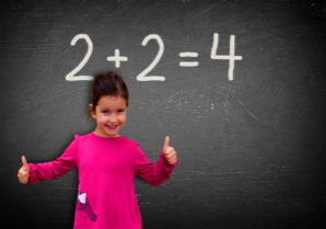 Proud assertive little girl solving a sum on blackboard - Learning and education concept