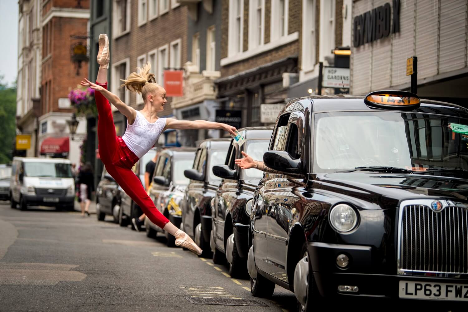 Dancer leaping while paying a London black cab driver