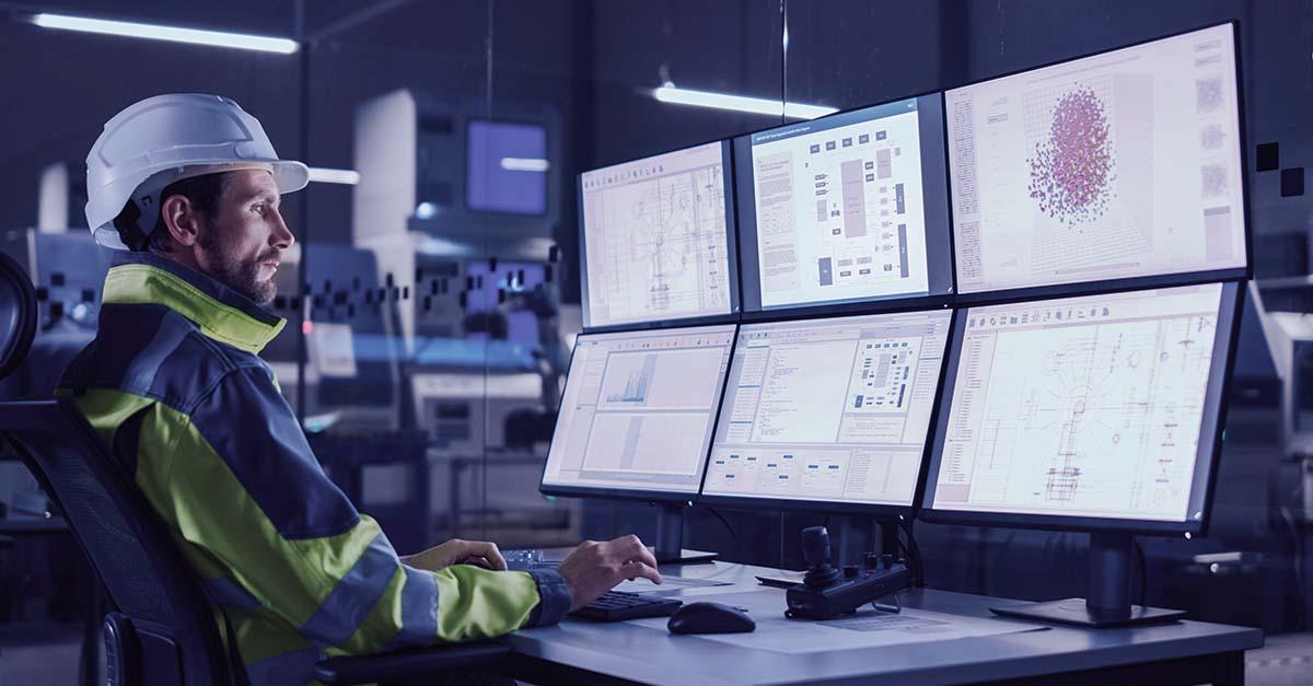 Homem branco de frente para 6 telas de computador em uma industria