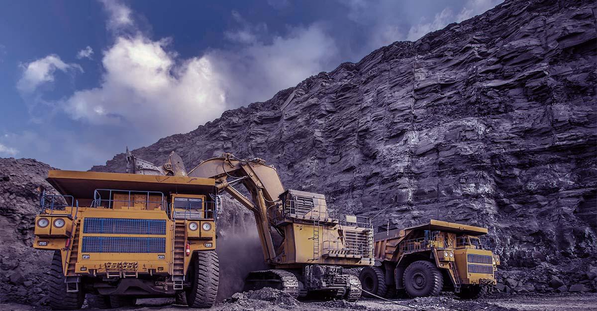 Escavadeira e caminhões amarelos em uma mineradora