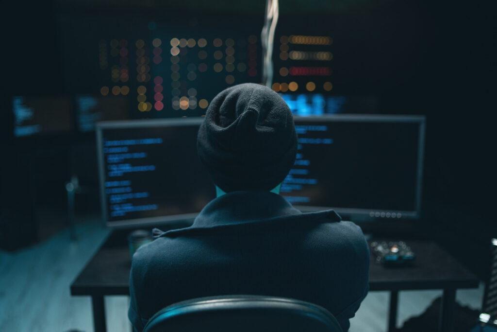 Imagem mostra homem encapuzado diante de dois monitores em um ambiente escuro.