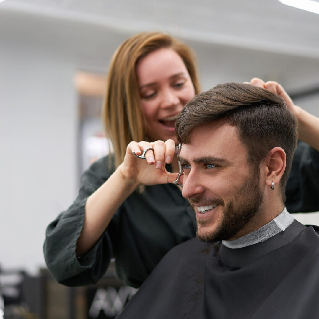 Stylish man sitting barber shop Hairstylist Hairdresser Woman cutting his hair Portrait handsome happy young bearded caucasian guy getting trendy haircut Attractive barber girl working serving client