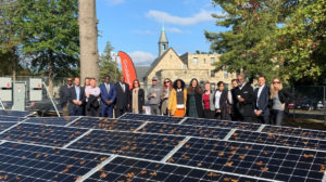 Group of people standing in front of House of Worship and behind array of solar panels