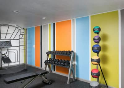 Fitness room with equipment and striped wall