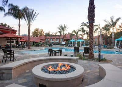 Fire pit in front of a pool with outdoor seating and palm trees