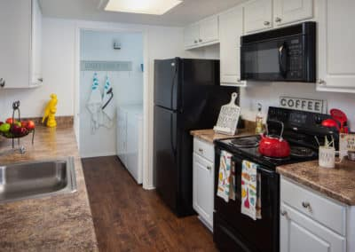 Kitchen with appliances, white cabinets, countertops, and wood flooring