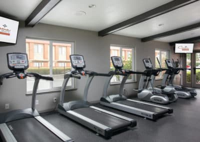 Fitness Studio with treadmills, windows, and televisions