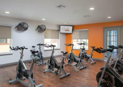 Cycling studio with windows, televisions, and fans