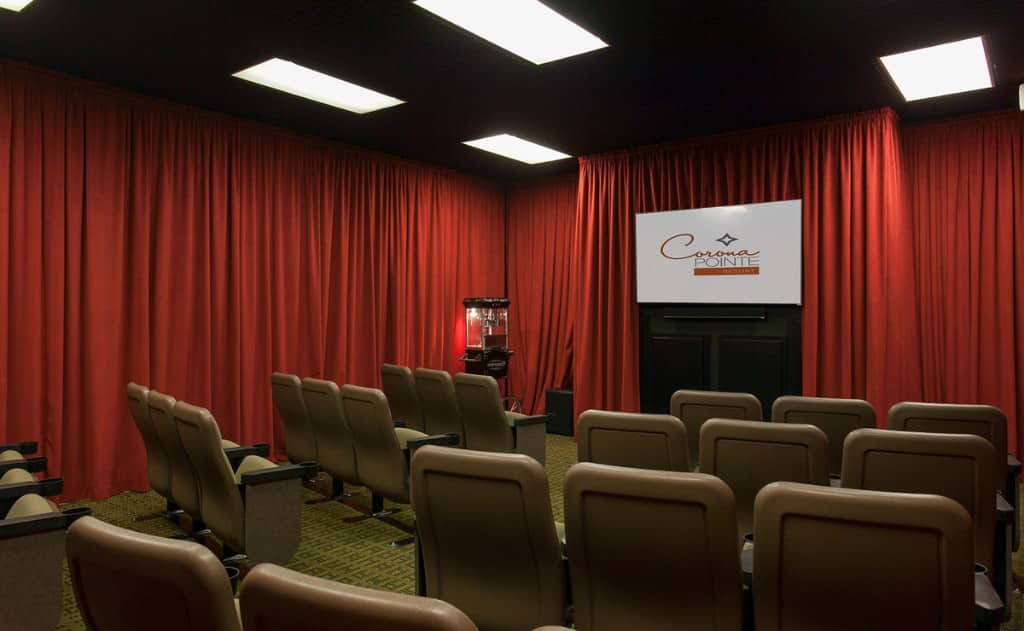 Movie room with chairs, red curtains, a projector screen, and a popcorn maker