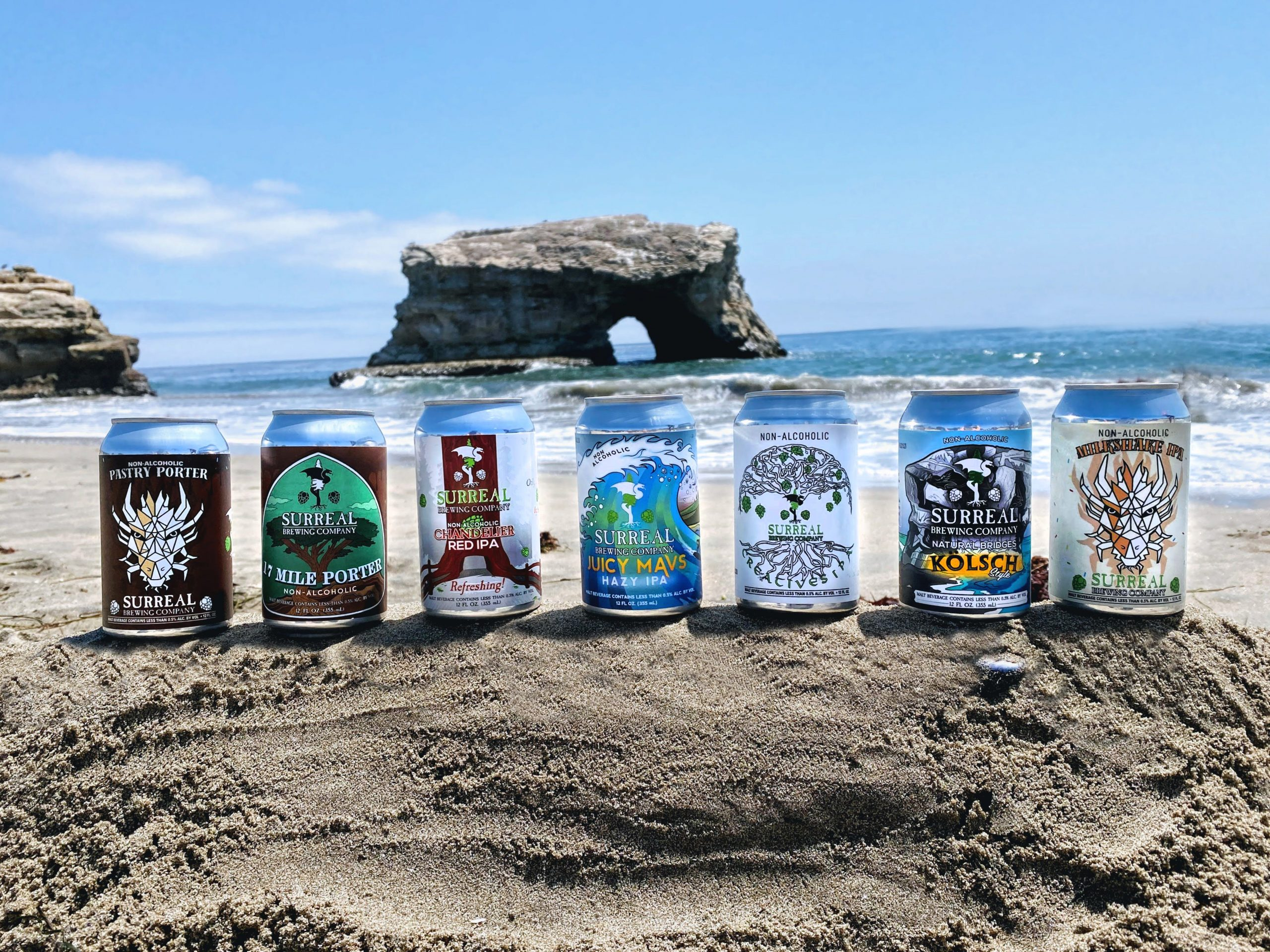 Non-alcoholic craft beer photo of all 7 Surreal Brewing Non-alcoholic IPA options on the beach