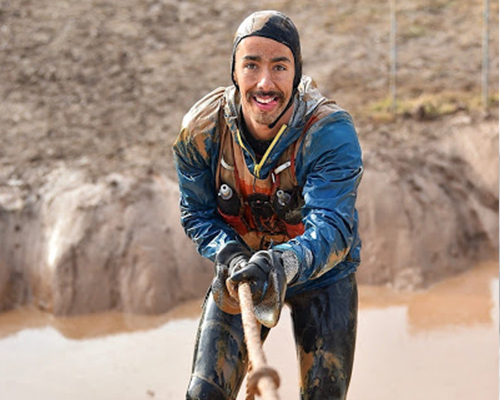 Surreal Brewing Tribe Member Adam climbing out of mud hole