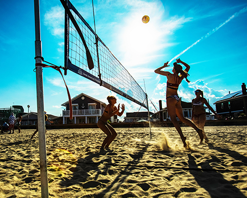 Surreal Brewing Tribe Member Aleksandra playing beach volleyball with two other women