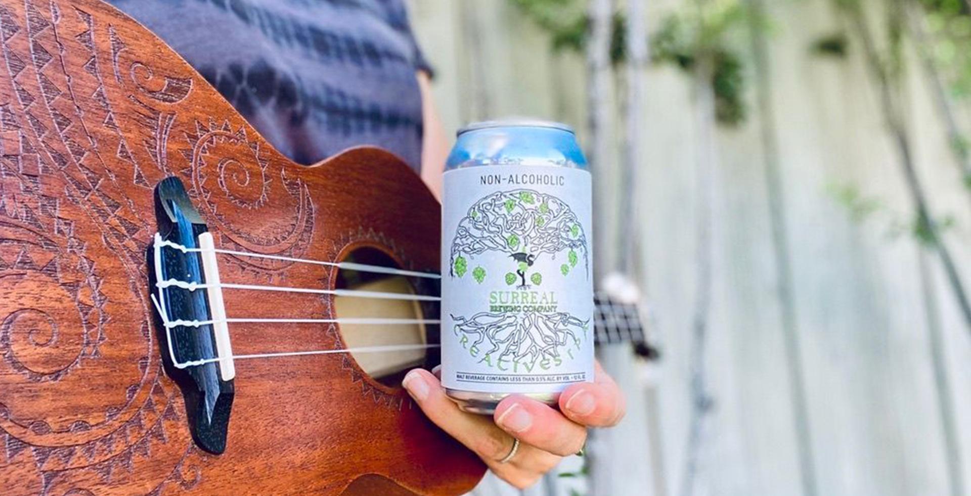 Man holding Creatives IPA non-alcoholic craft beer with ukulele