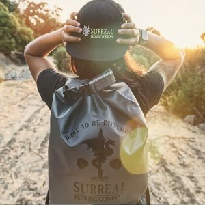 non-alcoholic craft beer brand ambassador showing off Surreal Brewing company merchandise