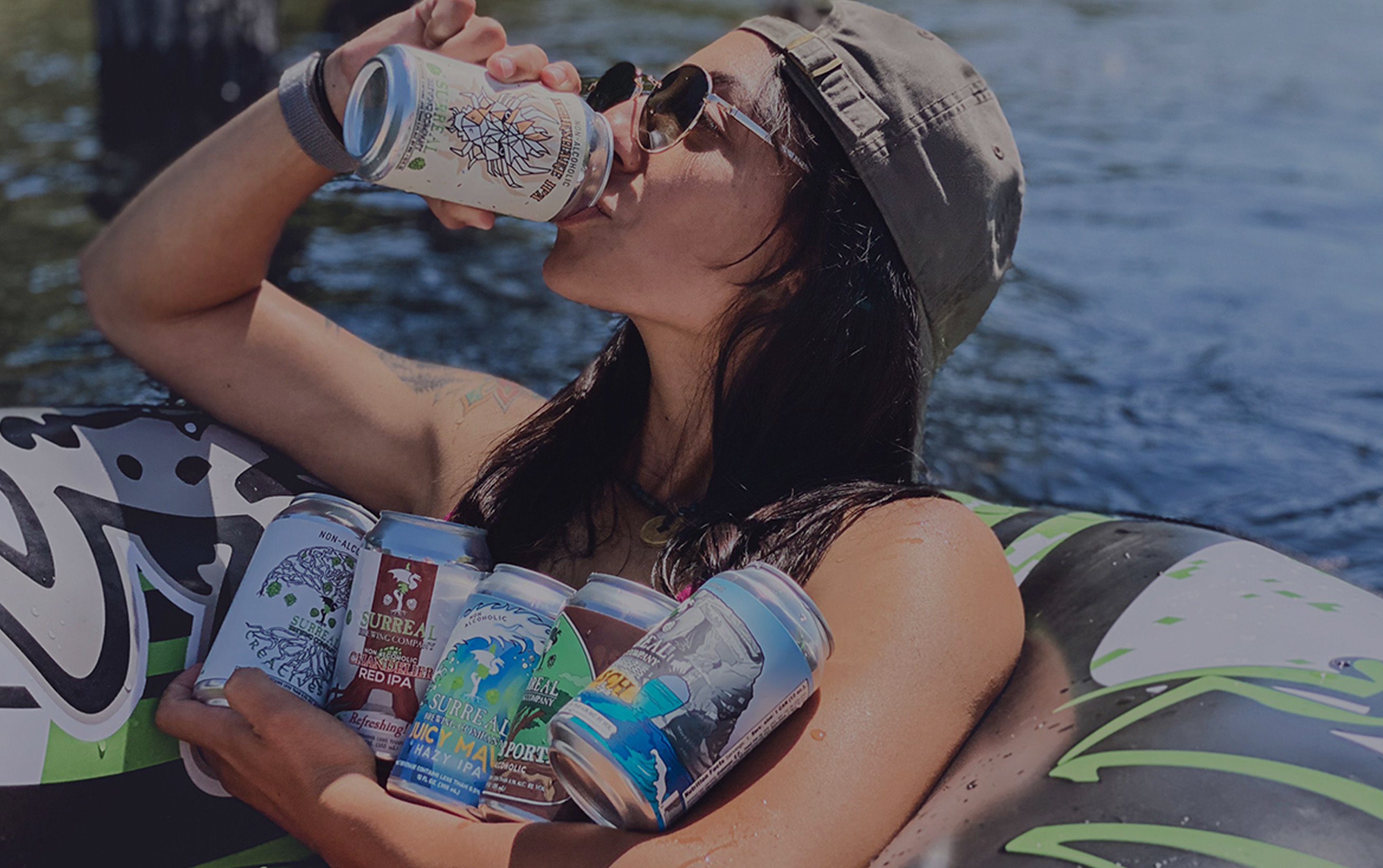 Girl enjoying Surreal Brewing Craft non-alcoholic beer on the river