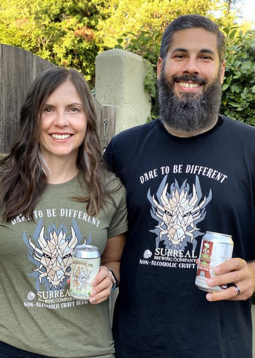 Photo of Surreal Brewing Owners Tammer and Donna holding two of their favorite beers