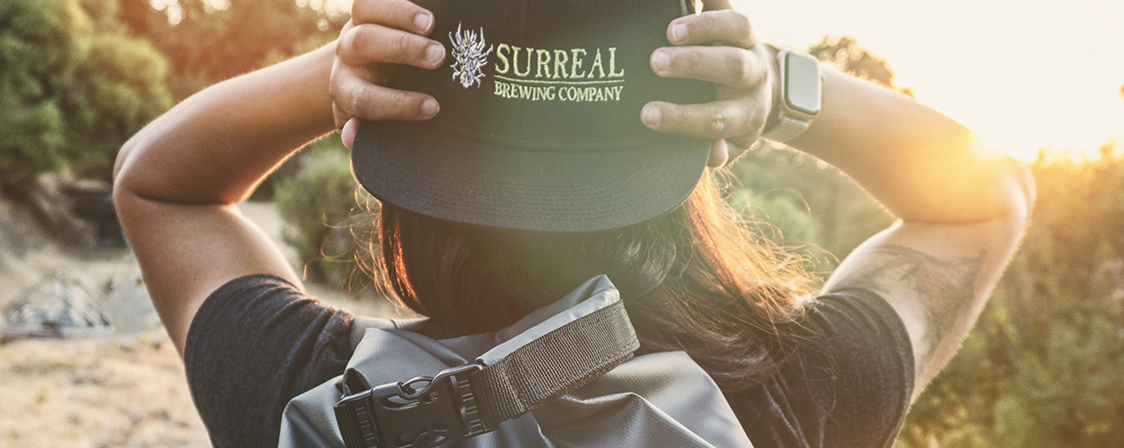 Girl holding Surreal Brewing Company Branded hat