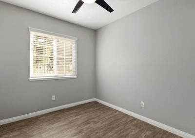 empty bedroom with grey walls and windows with blinds