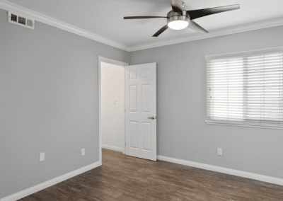 Empty bedroom with ceiling fan and window