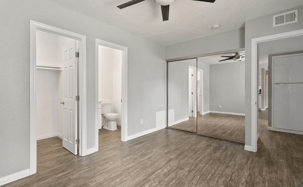 Empty bedroom with view into bathroom and closet space