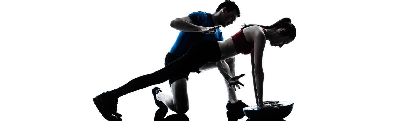Personal trainer spotting female client as she holds a plank on a Bosu ball